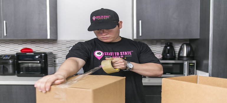professional packer is packing and labeling moving boxes