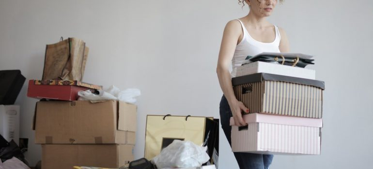 -a woman carying boxes