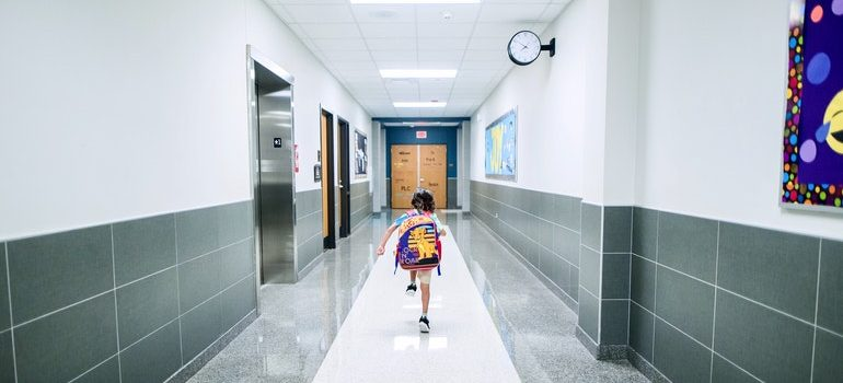 Boy running through a school hall as a result of parents who thought about things to know before moving to Long Island.