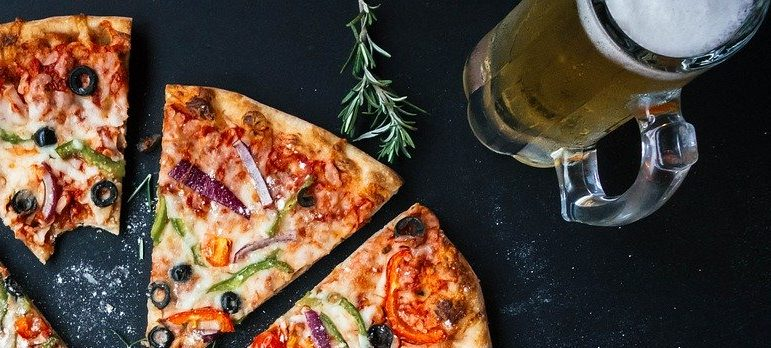 Sliced pizza and a pint of beer