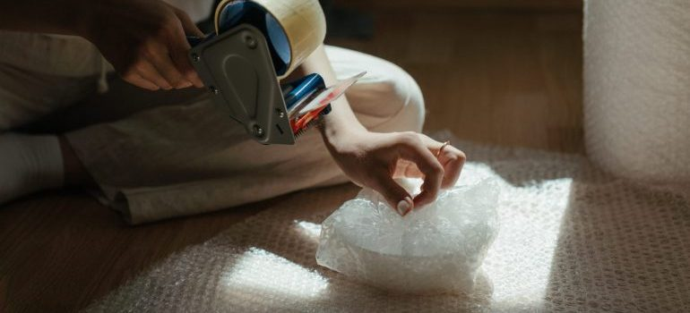 woman wrapping ceramics in bubble wrap