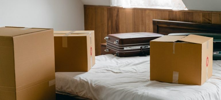 Boxes and a suitcase on a bed you will unpack before you settle after a move to Houston.
