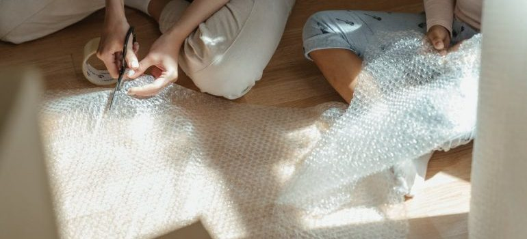 a woman cutting a bubble wrap and a kid playing with it