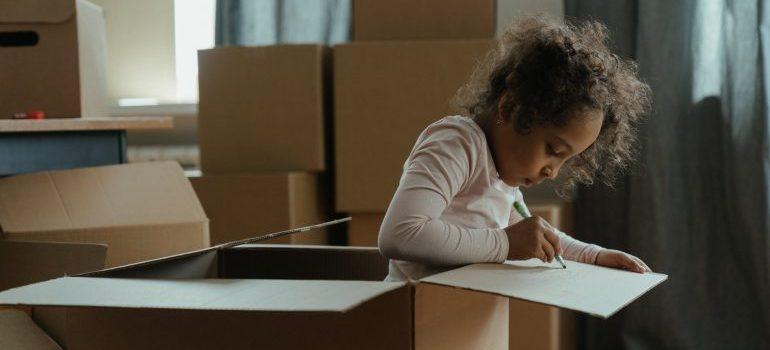 A girl playing in a cardboard box.