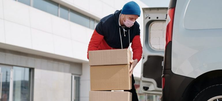 Man with a mask putting boxes in a truck