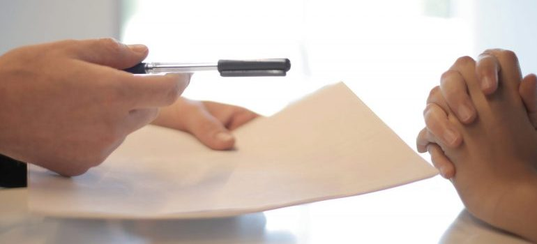 businessman-giving-contract-to-woman-to-sign