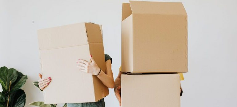 couple-carrying-cardboard-boxes-in-living-room