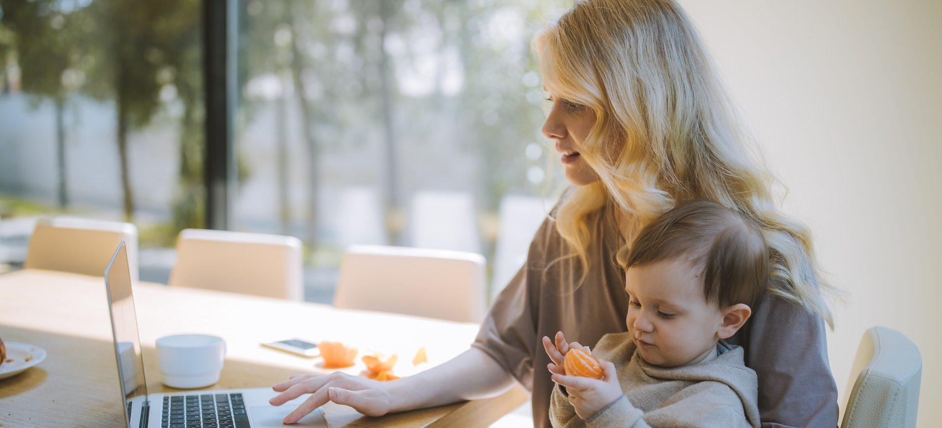 A woman holding her baby filling out an online form.