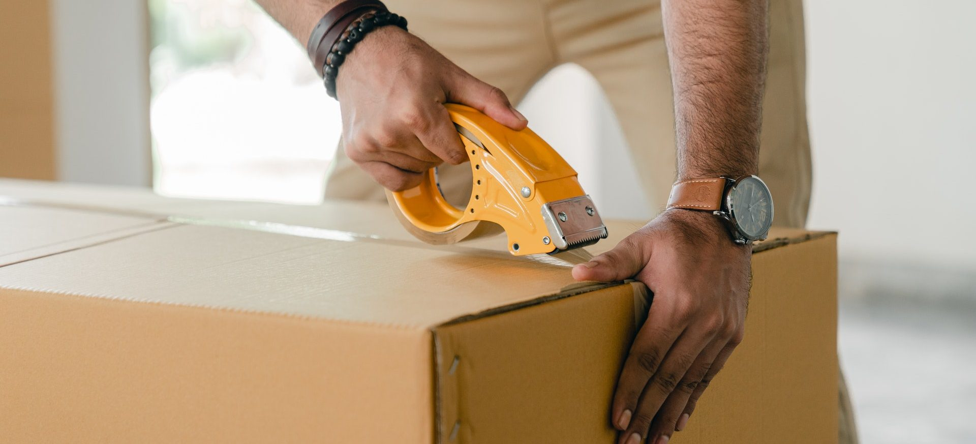 A man duct taping a moving box shut.