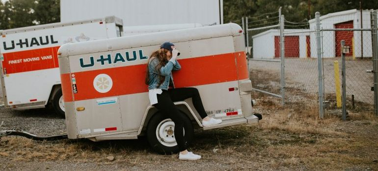 woman sitting on a u-haul mobile storage trailer