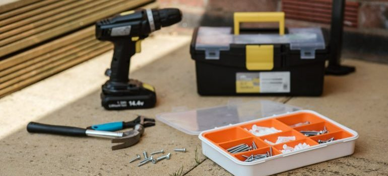 Drill and tools on the floor used to reassemble furniture after moving.
