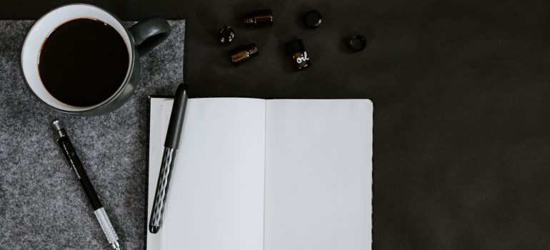 Notebook, pens and coffee on the table.