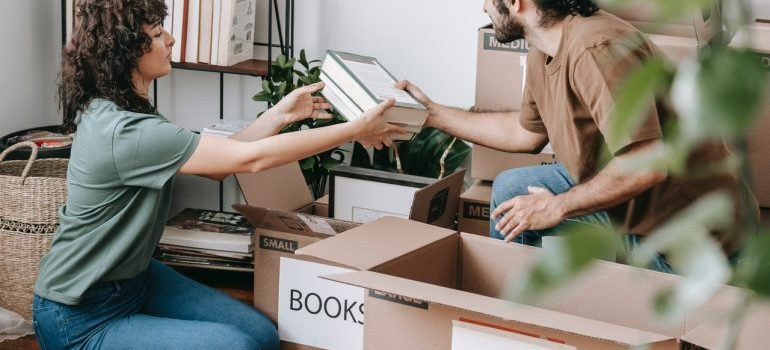 Woman and men packing books in the boxes