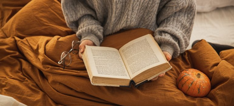 Woman in sweater with a book in hands sitting under the blanket