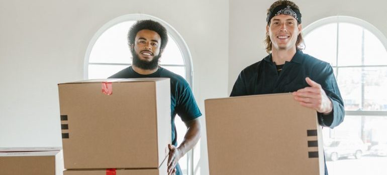 budgeting tips for interstate moving refer to the two professional men carrying boxes
