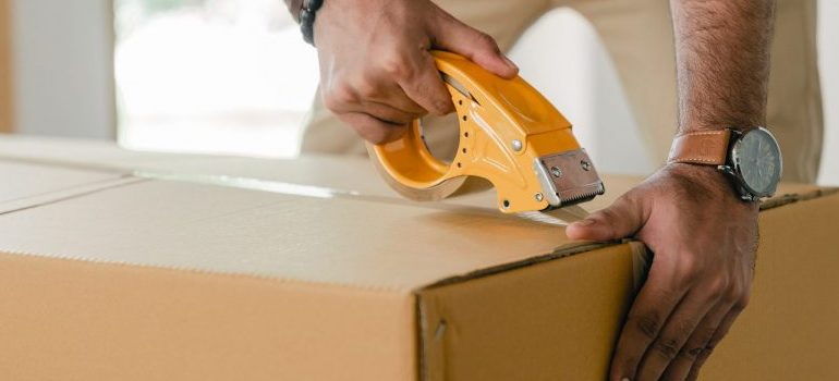 person sealing a packing box with tape