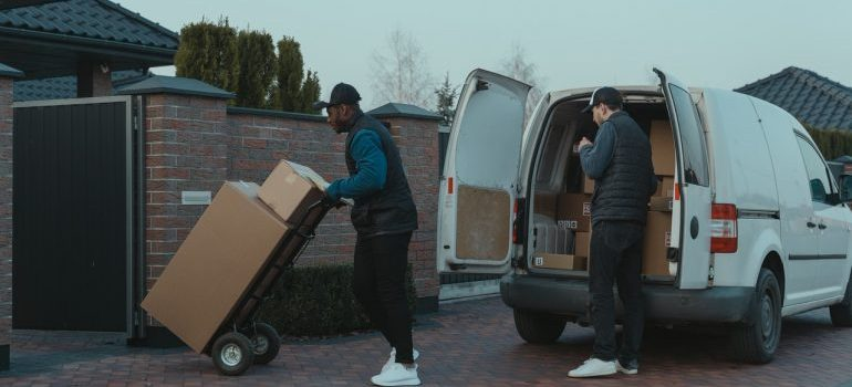 two men unloading the truck full of boxes during spring long distance move