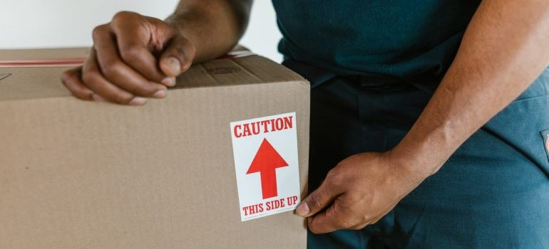 Mover holding a box with fragile items