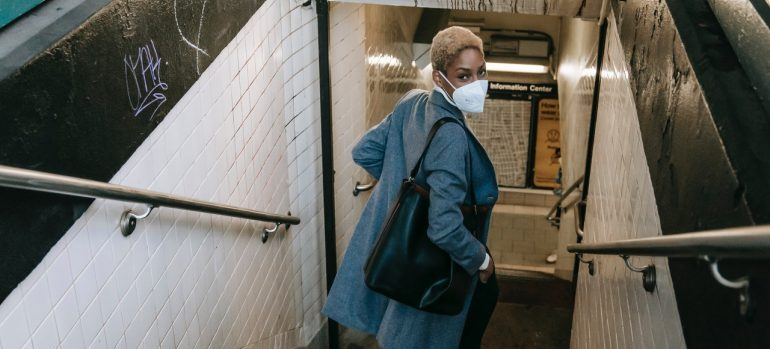 a woman going down the stairs to the subway