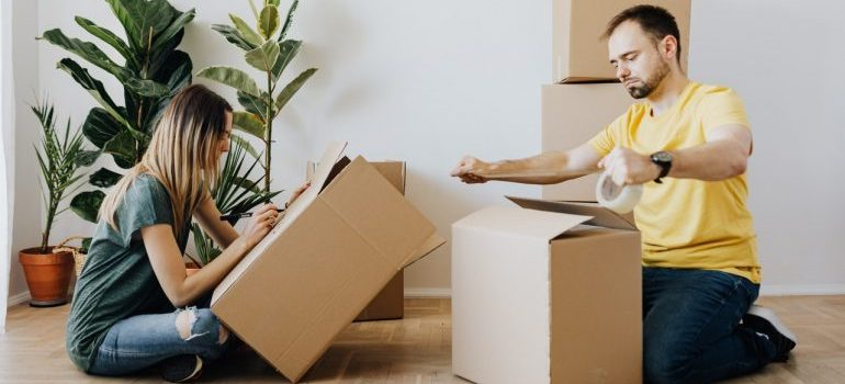 prepare well to relocate your Brooklyn condo like the woman labeling a box while a man is sealing the box with a tape