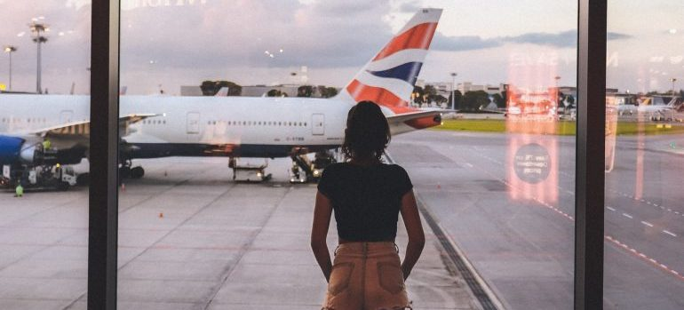 A girl in front of a window looking at a plane