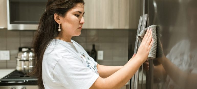 a woman in white t-shirt wiping the door of the fridge