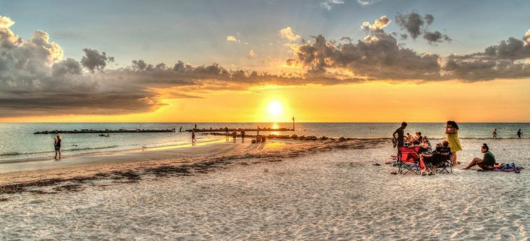 A group of people seating at the sandy beach in Tampa, during the sunset time.
