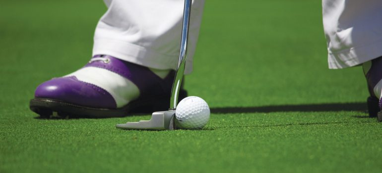 A shoe of the man, white golf ball and a golf club on the green grass of a gold field.