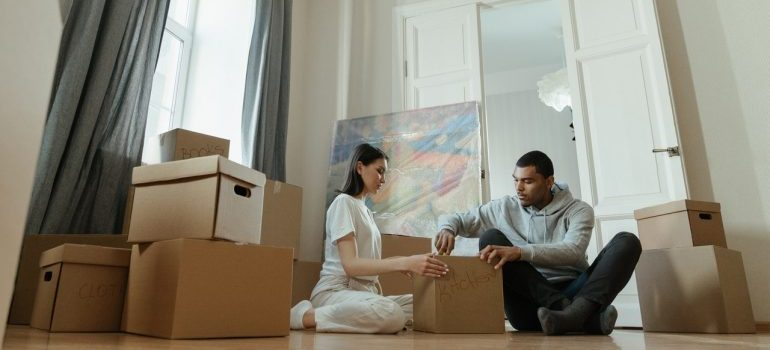 A couple sitting on the floor and packing things into a cardboard box surrounded by more cardboard boxes