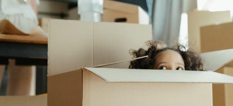 A little girl hiding inside a cardboard box