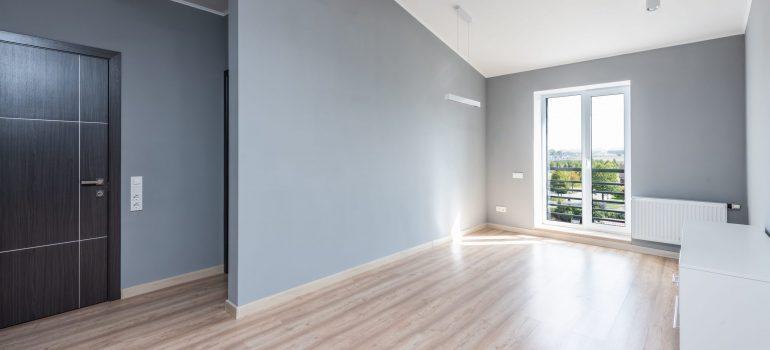 House interior of the empty house with grey walls, floor, side door and balcony glass door.