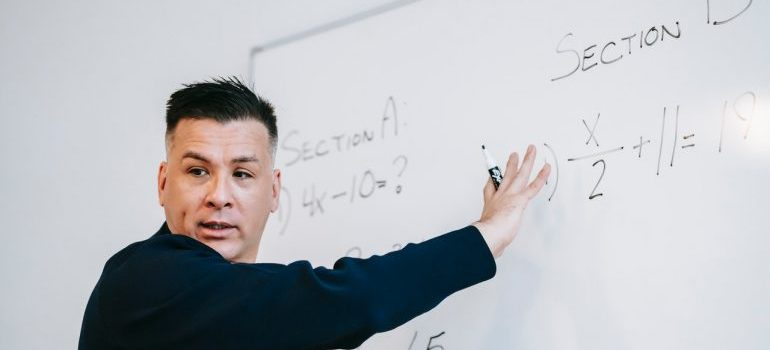 a man writing something on the white board and explaining the lesson