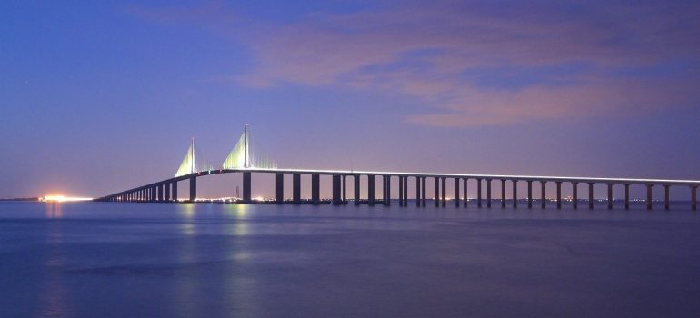 A bridge in the dusk, like a illuminated line between darkening ocean water and sky, that you can visit while you spend your first week in Tampa FL.