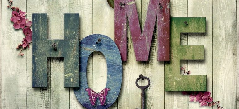 A wooden board with wooden letters reading HOME in different colors, a key, butterfly and some flowers.