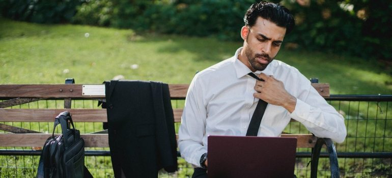 A man is sitting in a park on a bench and working on a laptop.
