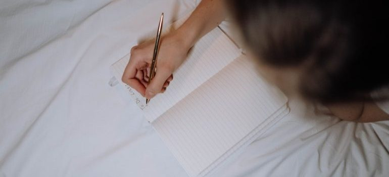 a woman writing something in her notebook