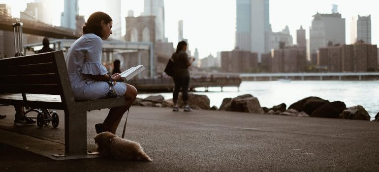 A girl sitting on a bench with her puppy inBrooklyn Bridge Park