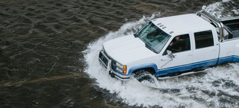 A car driviing on a flooded road