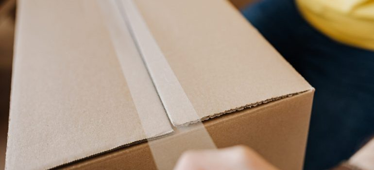 Person taping a moving box