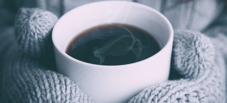 A person holding hot coffee